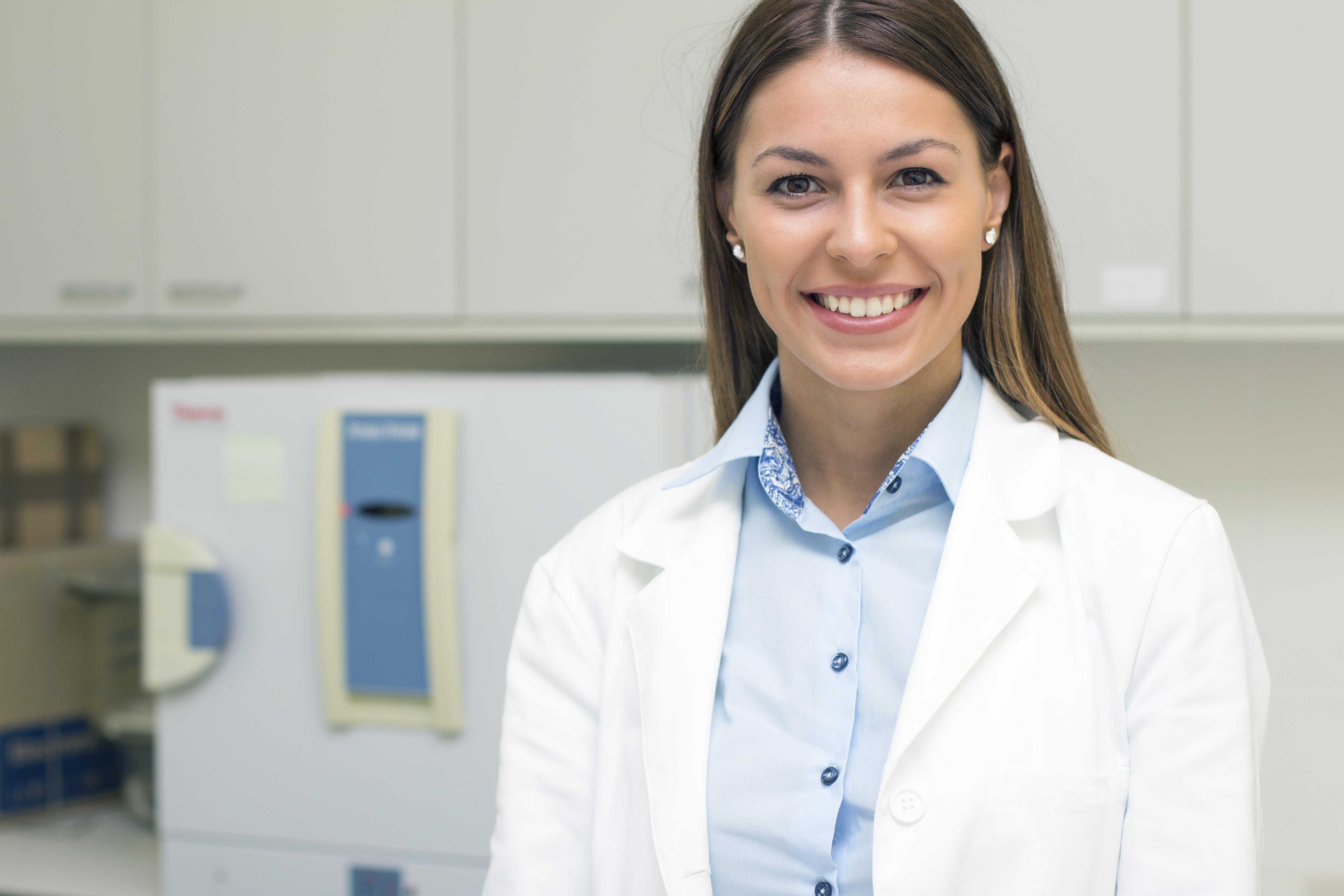 scientist-female-smiling-whitecoat-lab-equipment.jpg